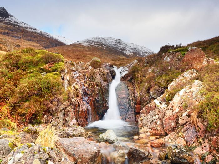 Rapids in small waterfall on stream, higland in scotland spring day. snowy cone of mountain