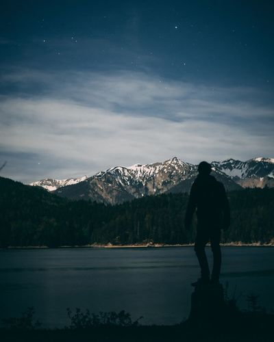 Rear view of man standing by lake against mountains and sky
