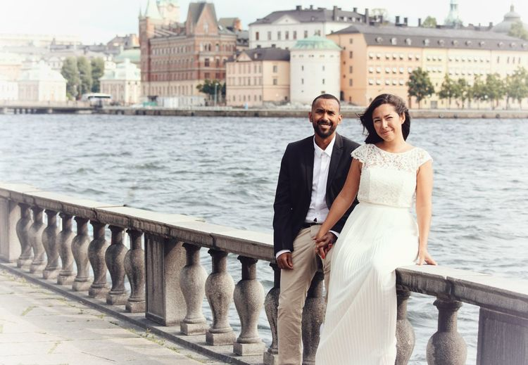 Portrait Of Couple Sitting On Retaining Wall By River Against Buildings