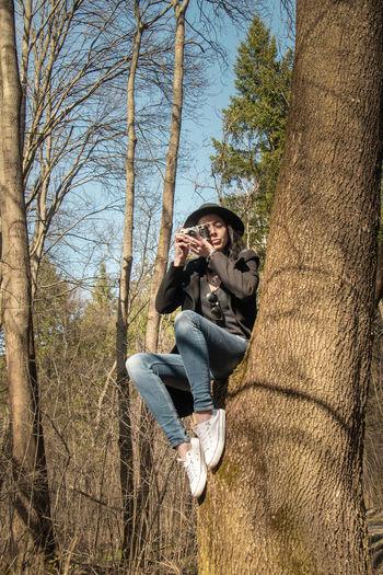 Man wearing sunglasses on tree trunk