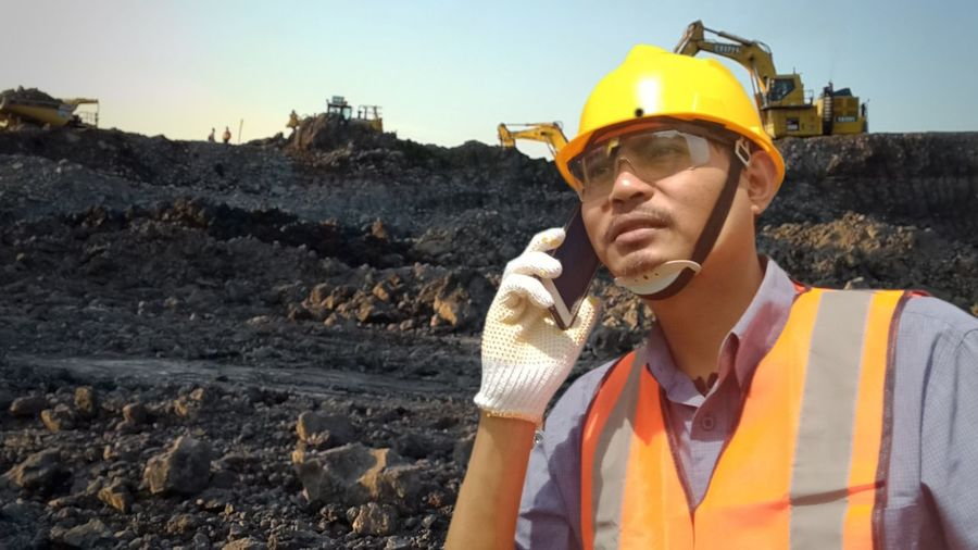 Portrait of man holding camera at construction site