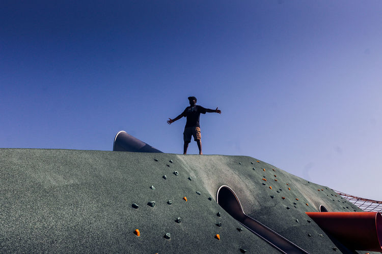 Low angle view of man standing on outdoor play equipment against clear blue sky