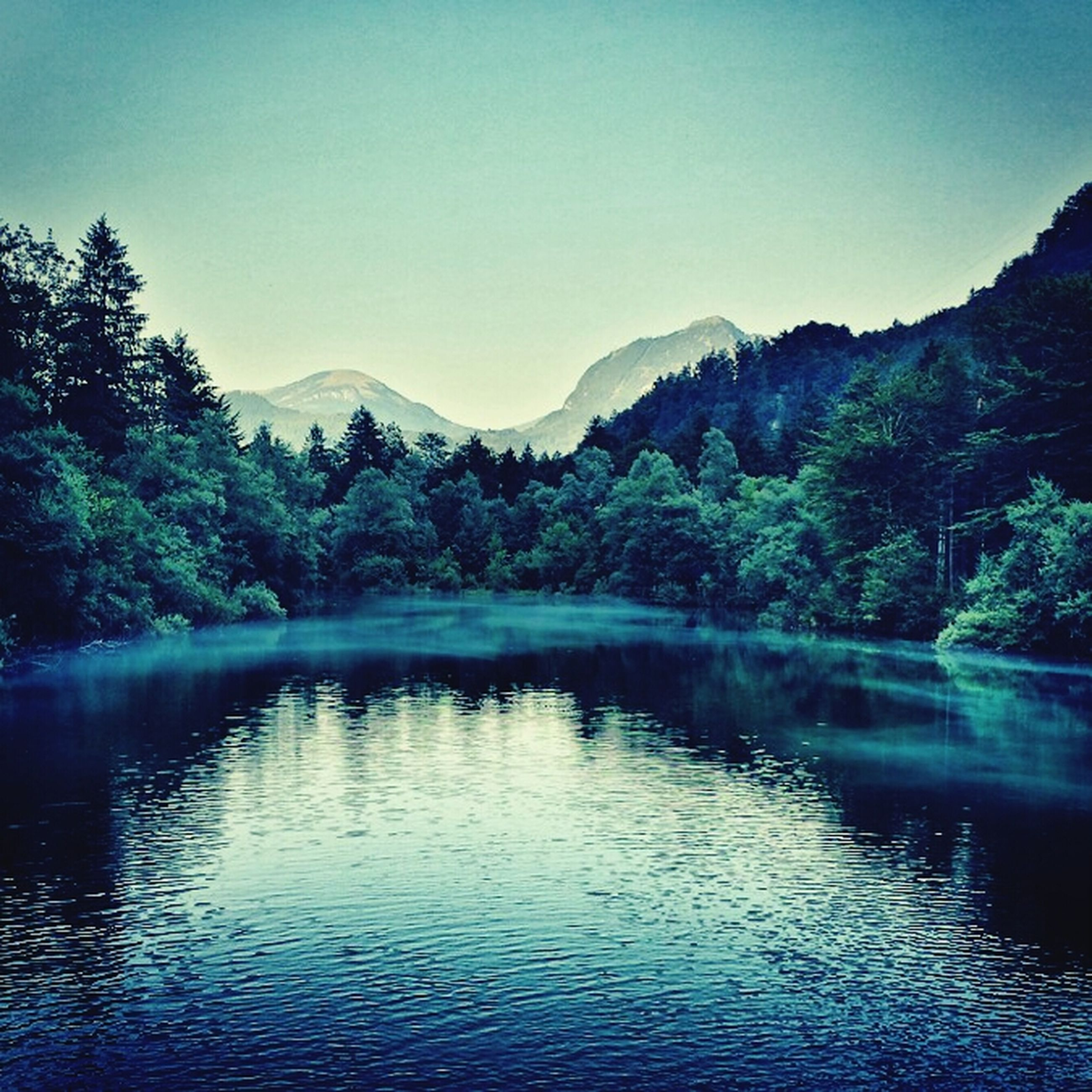 mountain, water, tranquil scene, lake, scenics, tree, tranquility, waterfront, mountain range, beauty in nature, clear sky, nature, reflection, idyllic, river, sky, forest, non-urban scene, outdoors, calm