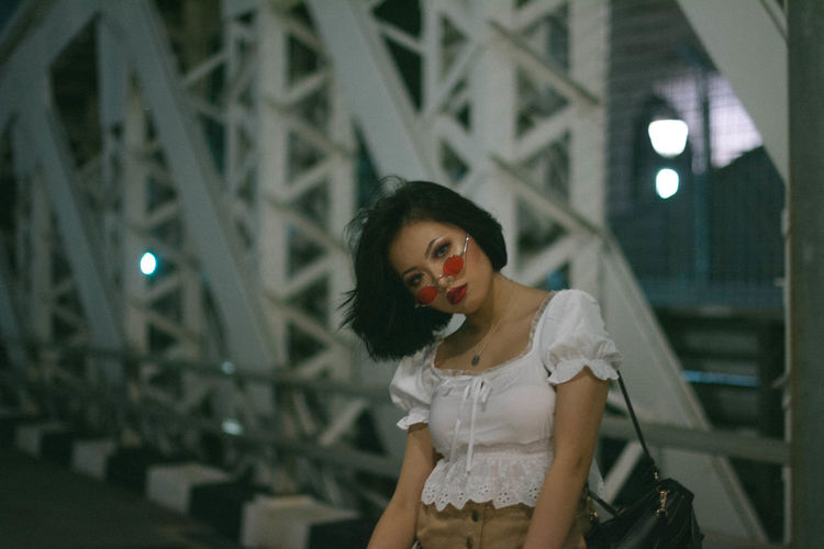Portrait of young woman with head cocked wearing sunglasses standing on bridge in city at night