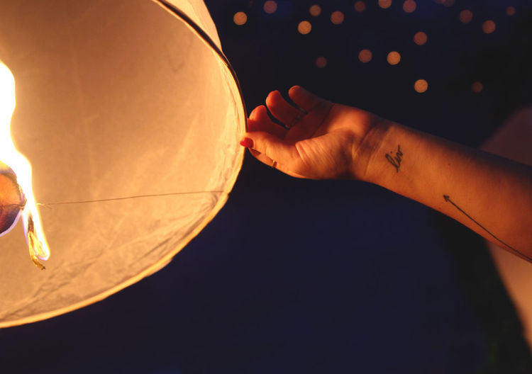 Cropped image of woman releasing paper lantern at night
