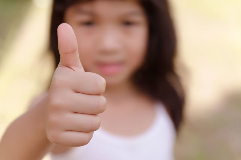 Girl gesturing thumbs up outdoors