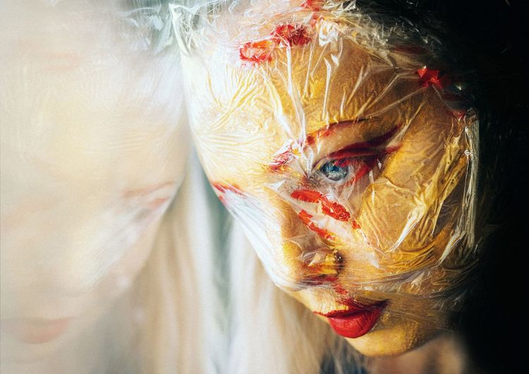Close-up of woman looking away with plastic and paint on face