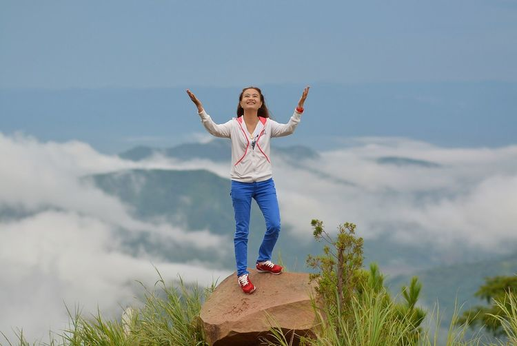 Woman Standing On Cliff Against Sky