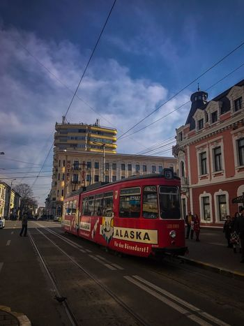 Sky Building Exterior Street City Transportation Architecture Built Structure Mode Of Transport Cloud - Sky Land Vehicle City Street Road Cable Car Public Transportation Tram Day Outdoors