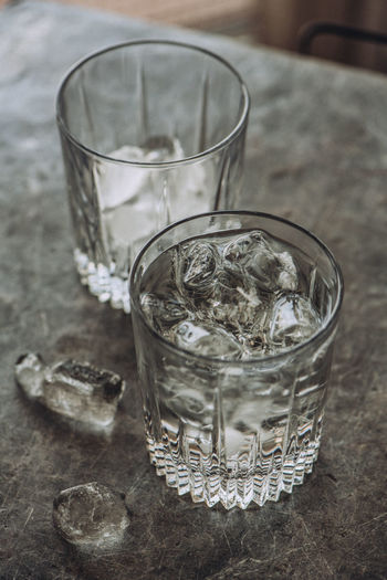 High angle view of drinks with ice cubes on table