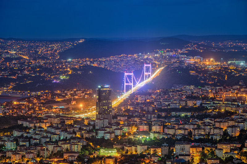Illuminated fatih sultan mehmet bridge in city at night
