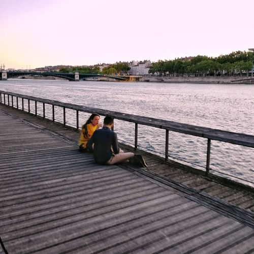 People sitting on pier over river against sky