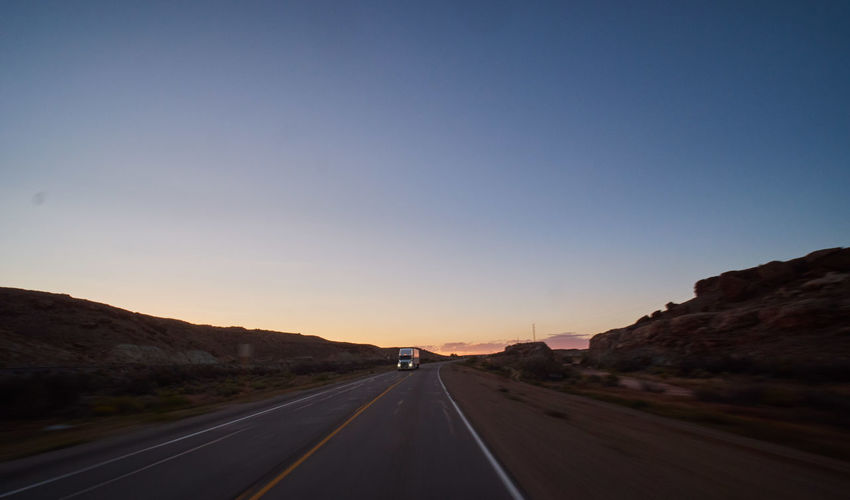 Empty road against clear sky at sunset