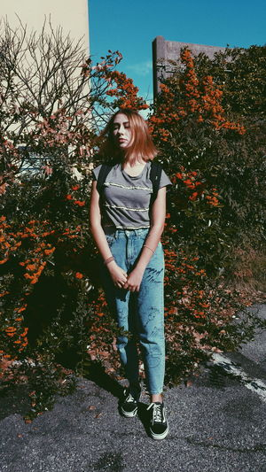 Young Woman Standing Against Plants At Park