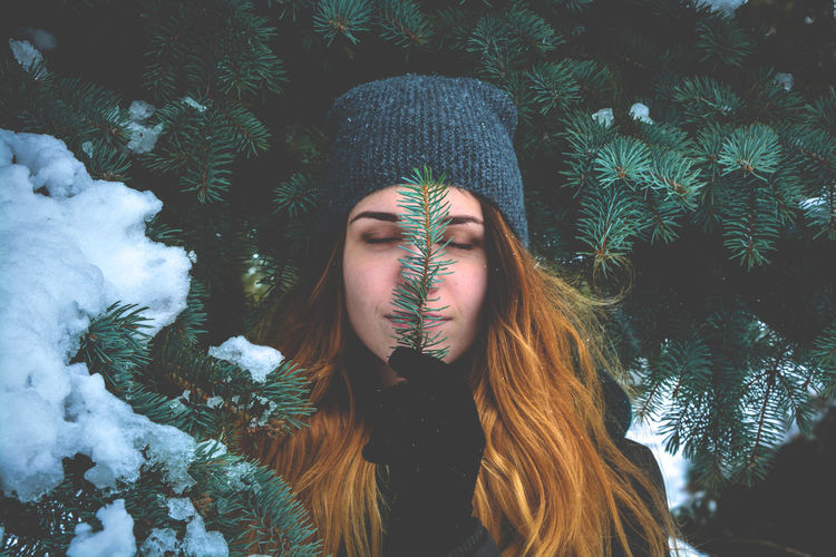 Young Woman With Eyes Closed Holding Pine Needles During Winter