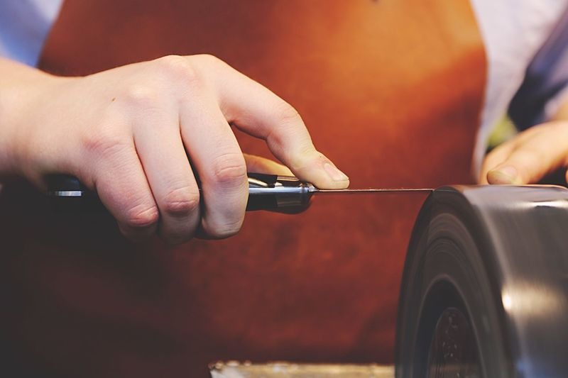 Cropped image of hand sharpening knife