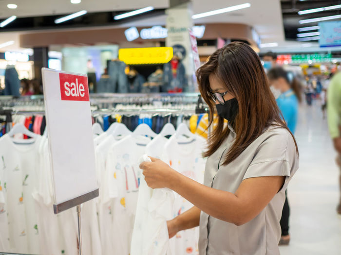 A woman wearing a protective mask while choosing a product in the mall. person