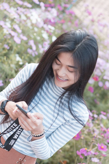 Smiling Woman Using Mobile Phone While Standing Against Flowering Plants