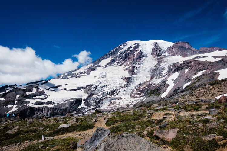 Snowed rocky mountain against blue sky