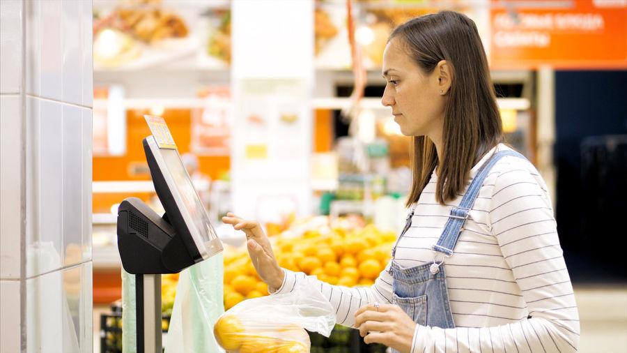 Woman weighing oranges at supermarket