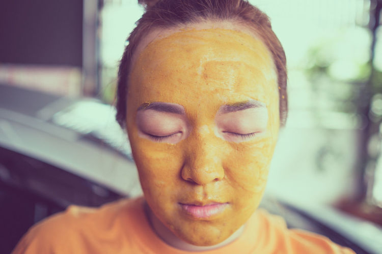 Close-up of young woman with facial mask at home