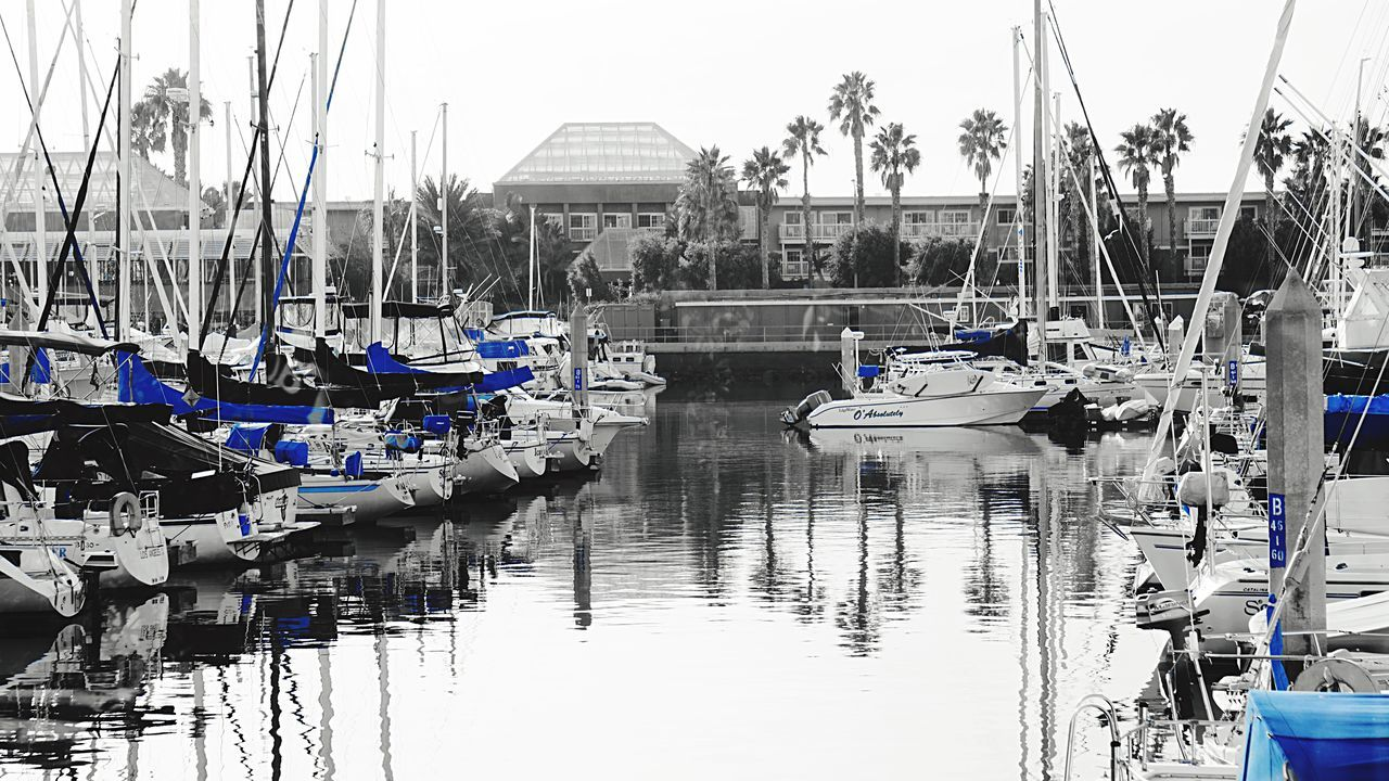 nautical vessel, water, moored, transportation, mode of transport, reflection, building exterior, built structure, no people, architecture, outdoors, day, harbor, mast, nature, tree, sky