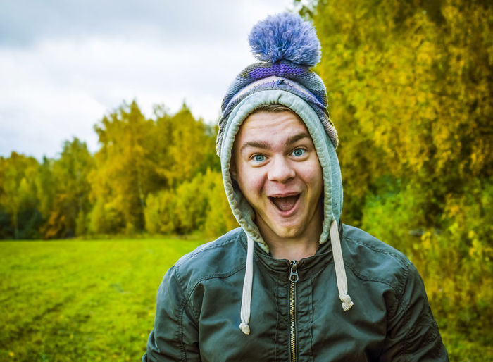 Portrait of happy young man with mouth open standing at park