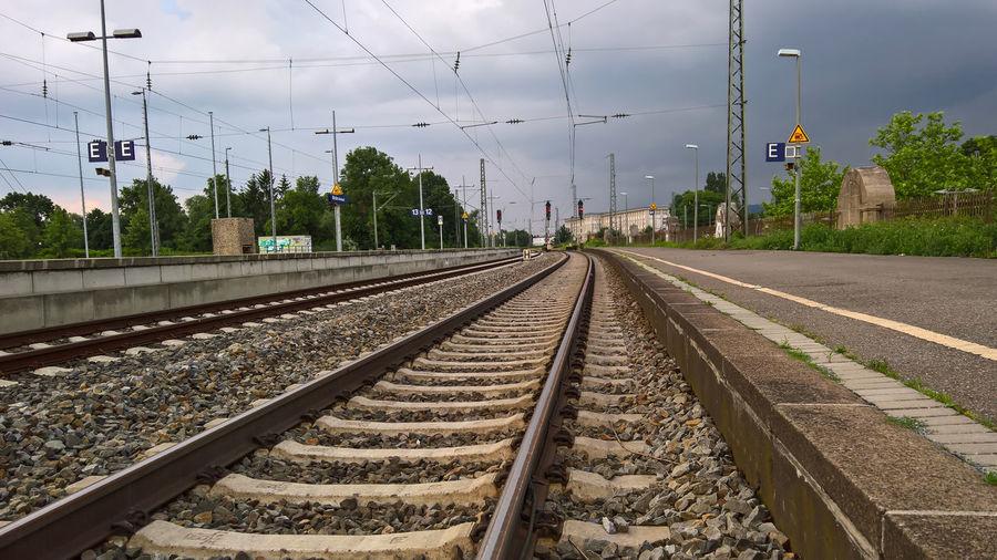 Railroad tracks by platform against sky