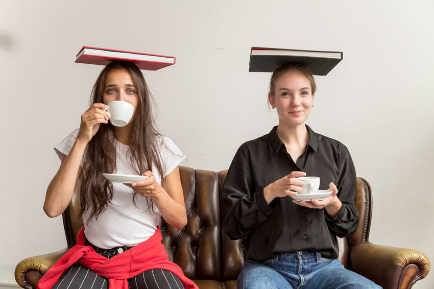 Two young women sitting side by side on sofa balancing books on their head and drinking coffee Drink Cup Young Adult Food And Drink Mug Young Women Indoors  Coffee Cup Coffee - Drink Holding Balancing Book Concept Studio Shot Natural Lighting Two People Caucasian Two Women Side By Side Sitting Beautiful Women Looking At Camera Women Coffee Middle Eastern Woman