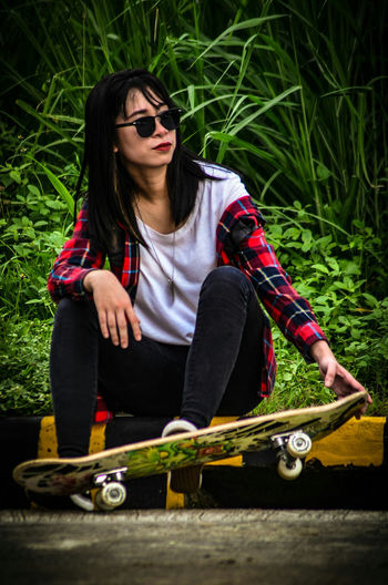 Rockstar Rockstar Eyeglasses  Sitting One Woman Only Young Adult Adult Full Length Brown Hair One Young Woman Only Skateboard Women One Person People Casual Clothing Outdoors Day Relaxation Only Women Young Women Adults Only Grass