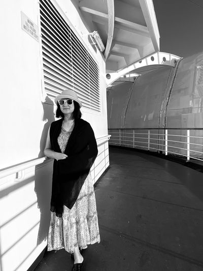 Woman wearing sunglasses and hat in boat deck