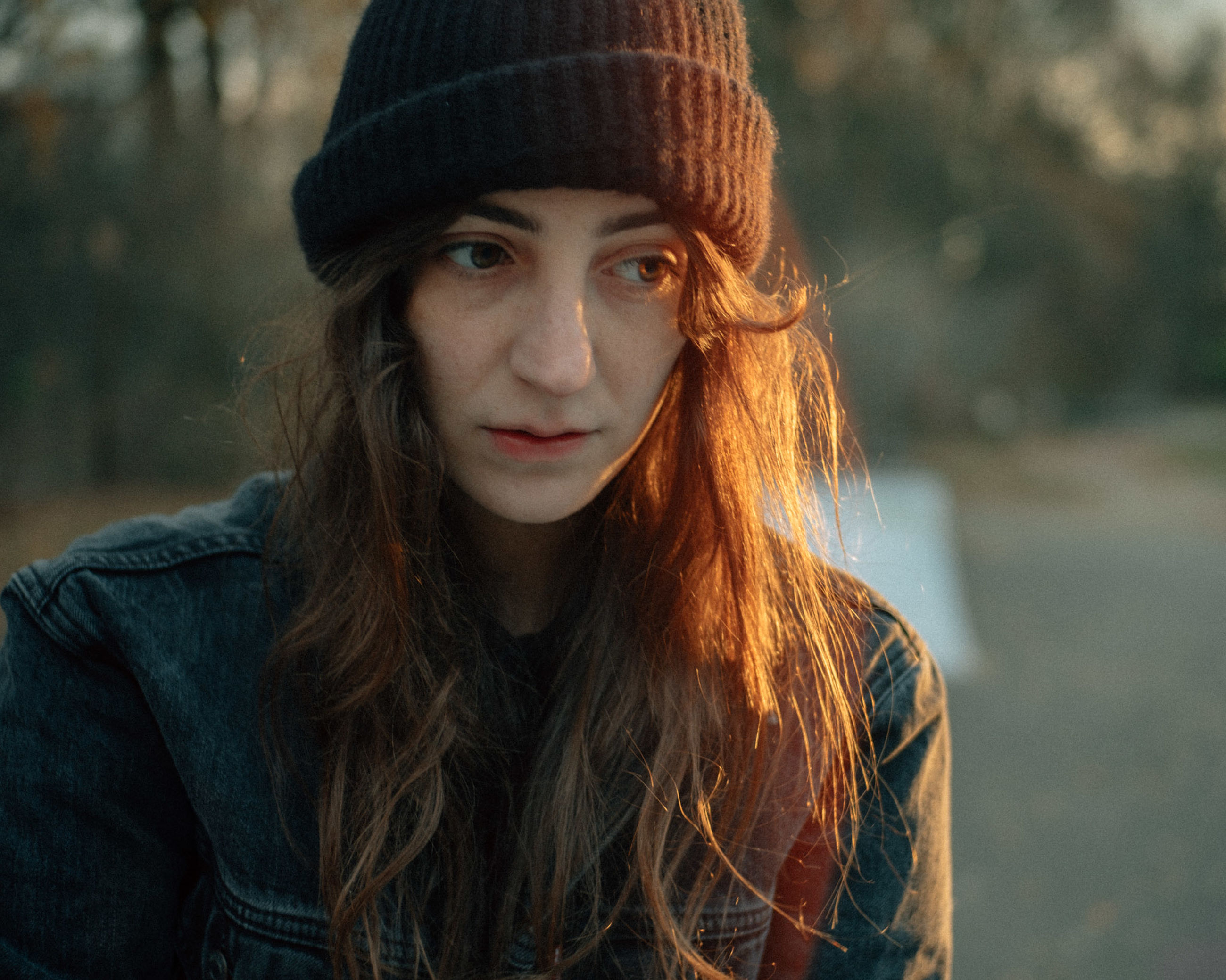 portrait, one person, looking at camera, hat, young adult, front view, real people, young women, focus on foreground, long hair, clothing, headshot, lifestyles, hairstyle, hair, beauty, beautiful woman, leisure activity, knit hat, warm clothing, outdoors, contemplation