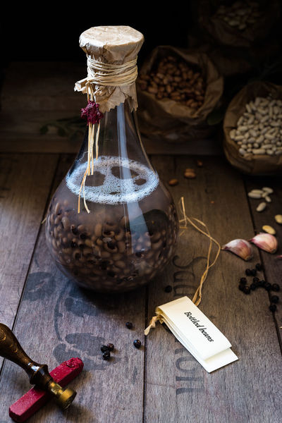 eye beans cooked in a bottle with sage and garlic Bean Bottle Bottle Art Chiaroscuro  Cooking Cow Pea Dark Garlic Indoors  Italian Food Leaf Long Cooking No People Old-fashioned Paper Pepper Red Rustic Sage Sealed Sealing Wax Tavern  Tradition Twine Wood - Material First Eyeem Photo