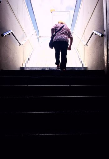 Rear view of man standing on staircase