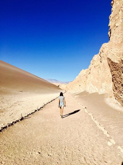 Rear view of woman walking on footpath at desert against clear blue sky