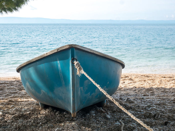 Blue boat with rope on the beach close to the blue sea background Boat Sea Vessel Blue Water Nautical Vessel Sky Tranquility Beauty In Nature Nature Scenics - Nature Day No People Transportation Horizon Over Water Mode Of Transportation Outdoors Rowboat Small Beach Travel Tourism Summer Coast Coastline Nobody Empty Makarska Riviera Dalmatia Croatia Europe Adriatic Sea Mediterranean  Scenics Vacations Holiday Calm
