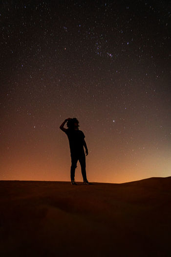 Man staring at the stars in the desert