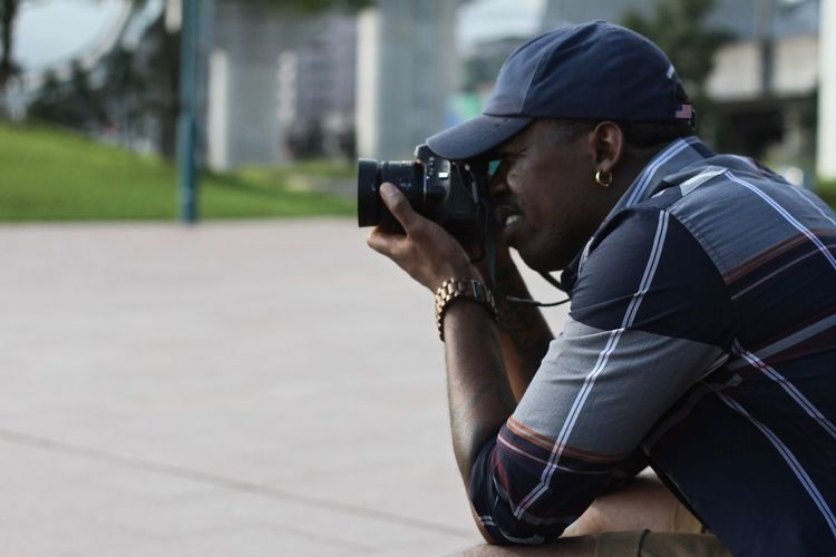 Side View Of Man Photographing On Street Using Camera