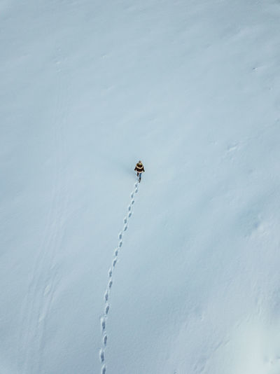 Aerial view of woman walking on snow covered field