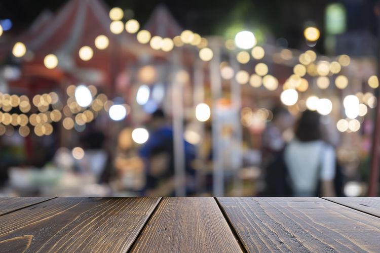 Defocused image of illuminated bench by railing at night