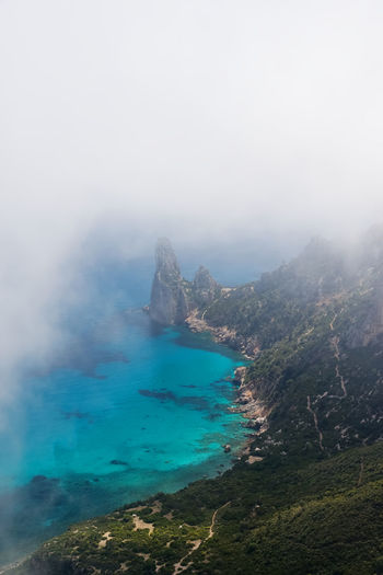 High angle view of sea and mountains against sky in sardinia