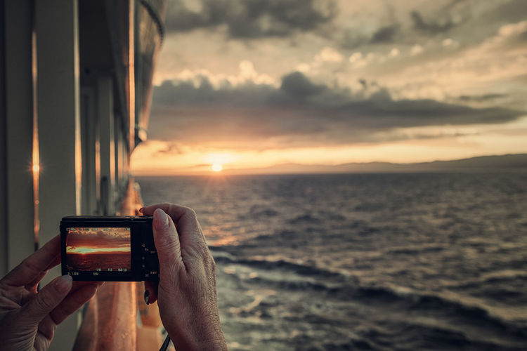 Cropped hand photographing sea from boat during sunset