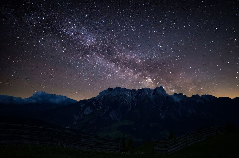 Scenic view of mountains against star field in sky at night