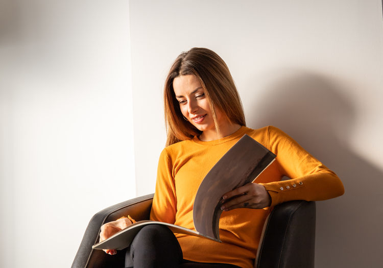 Young woman sitting on chair against wall at home