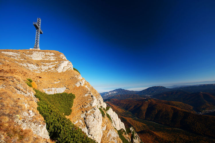 Low angle view of cross on bucegi mountains against clear blue sky