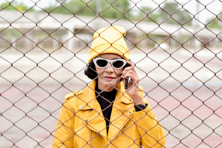 Portrait of woman talking on phone while standing by chainlnk fence