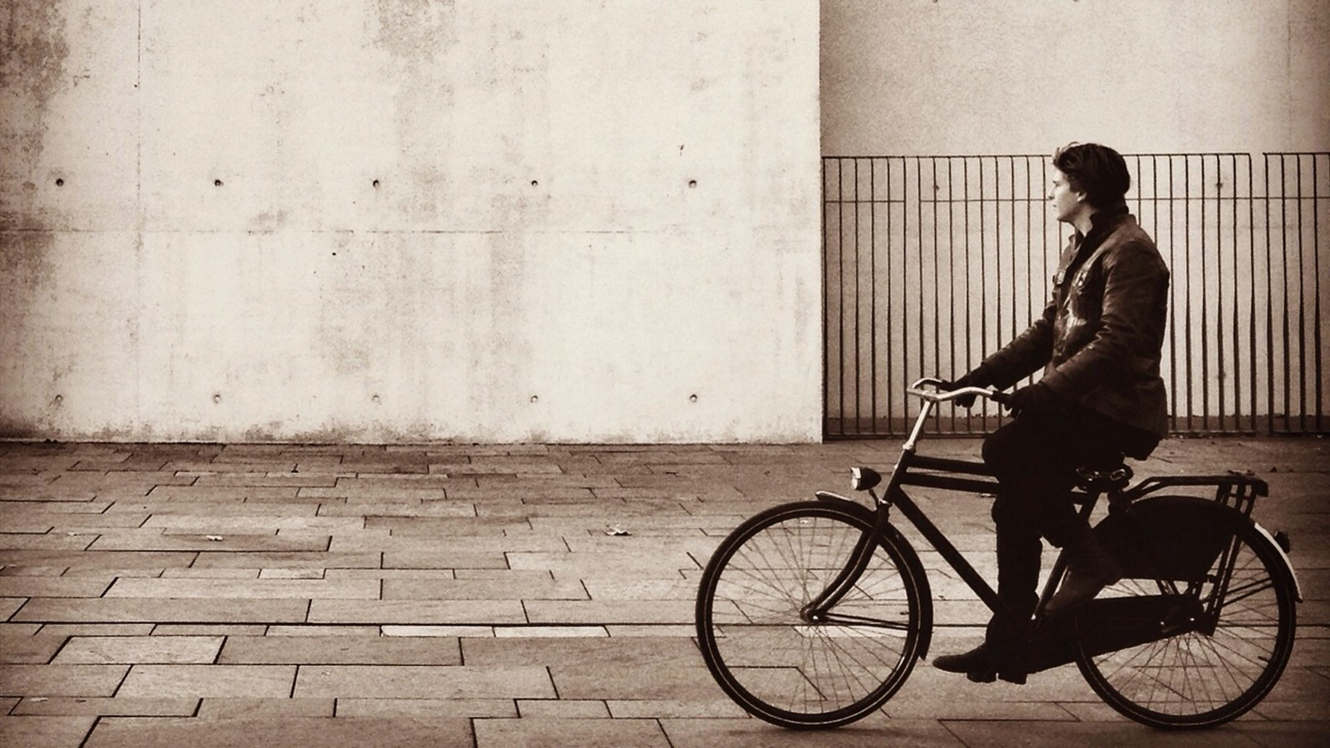 bicycle, mode of transport, transportation, full length, land vehicle, lifestyles, architecture, riding, built structure, side view, casual clothing, leisure activity, building exterior, men, leaning, wall - building feature, wall, stationary
