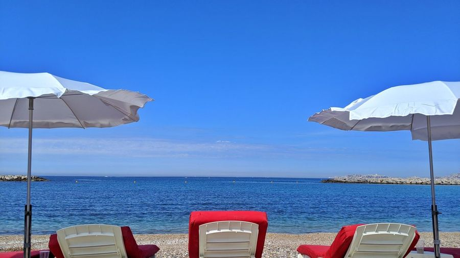 Deck chairs by sea against blue sky