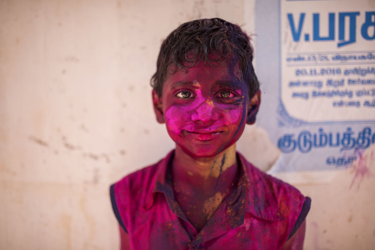 looking at camera, portrait, text, front view, real people, one person, focus on foreground, communication, lifestyles, standing, day, close-up, holi, outdoors
