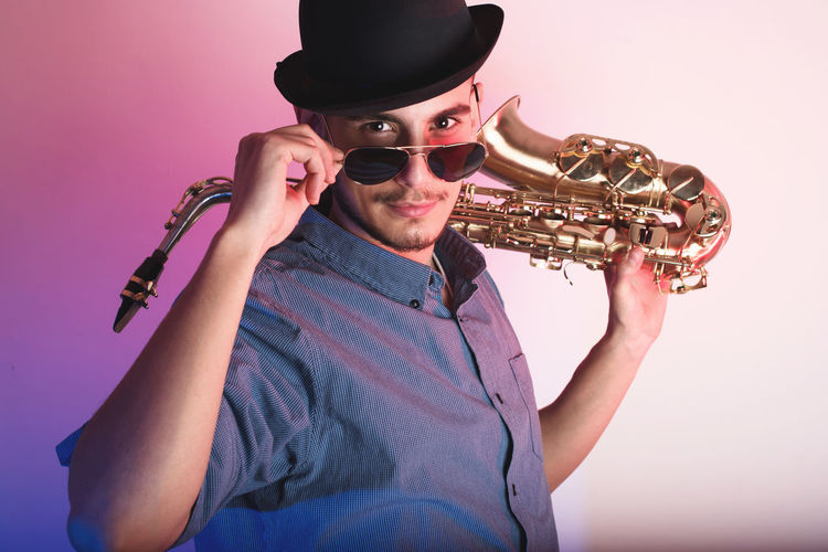 Portrait of man holding saxophone wearing hat